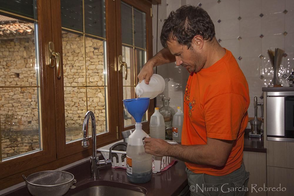 Andrés rellena la garrafa con anís y echa la canela en rama y los granos de café