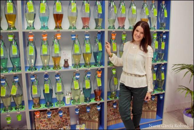 Nurilove con las botellas de fragancias como fondo
