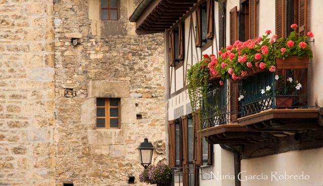 Casas típicas con sus balcones llenos de flores y color